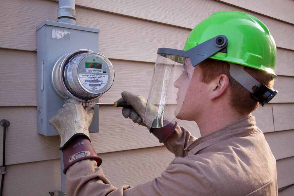David Graft of Wellington Energy Inc, works to install a new watthour meter at a residence in Portland, OR.